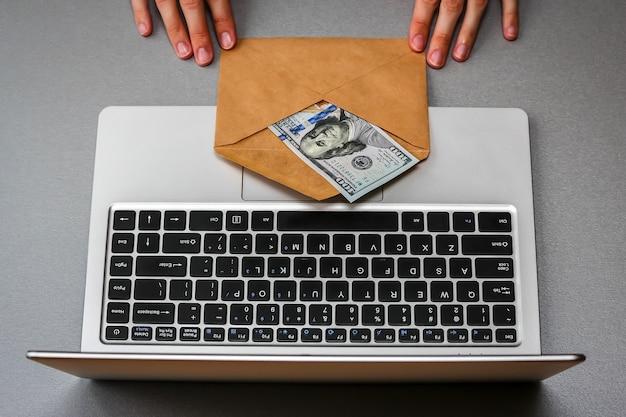 Крупным планом вид конверта с сто долларовой банкноты и клавиатуры ноутбука.