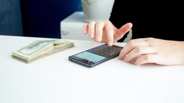 電卓でお金を数える女性会計士のクローズアップビュー。