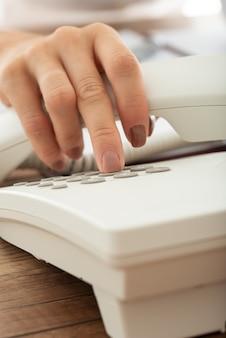 Крупным планом вид женской руки, набирающей номер телефона с помощью стационарного телефона.