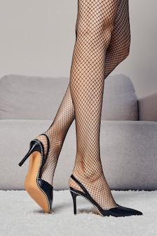 プロフィールで部屋に沿って歩く女性の脚のクローズアップビュー