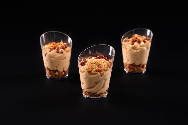 Крупным планом вид свежего домашнего сладкого кремового десерта из мюсли в трех маленьких очках подряд, изолированных на черном фоне. вкусное парфе, украшенное сверху коричневыми шариками и шоколадными взбитыми сливками.
