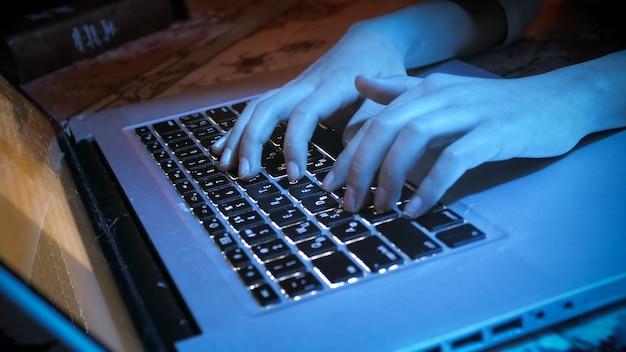 밤에 노트북 키보드에 입력하는 여자 손의 근접 촬영보기.
