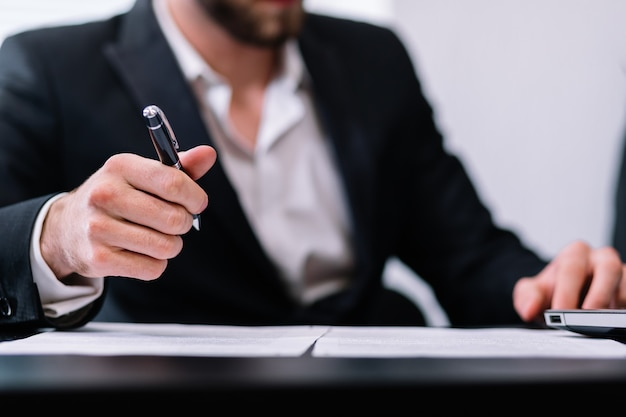 사업가 또는 펜으로 문서를 서명하는 변호사의 손의 근접 촬영보기.