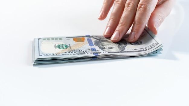 白い机の上のお金のスタックからドル紙幣を取る手のクローズアップビュー。