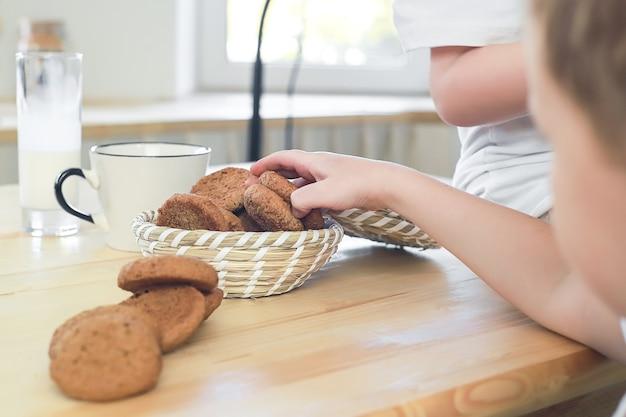 Крупным планом вид ребенка рука берет печенье из корзины, стоящей на кухонном столе здоровый завтрак