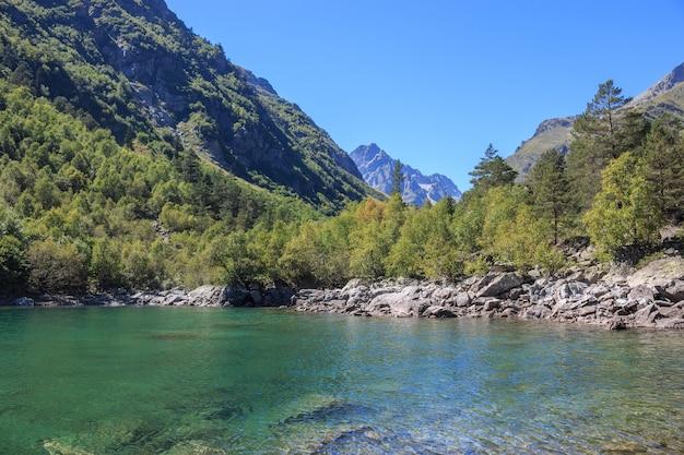 山、国立公園ドンベイ、コーカサス、ロシア、ヨーロッパの湖のシーンのクローズアップビュー。サンシャインの天気、青い空、遠くの緑の木々。カラフルな夏の日、時間