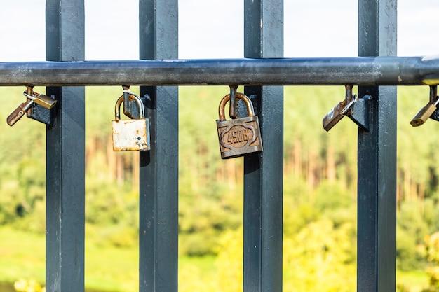 다리 울타리에 매달려 사랑 자물쇠의 근접 촬영 보기.