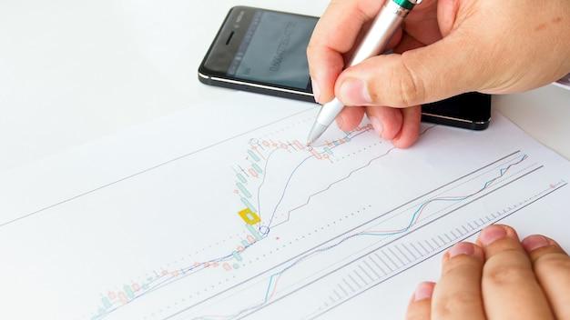 株式市場の財務分析を行う男性銀行家のクローズアップビュー