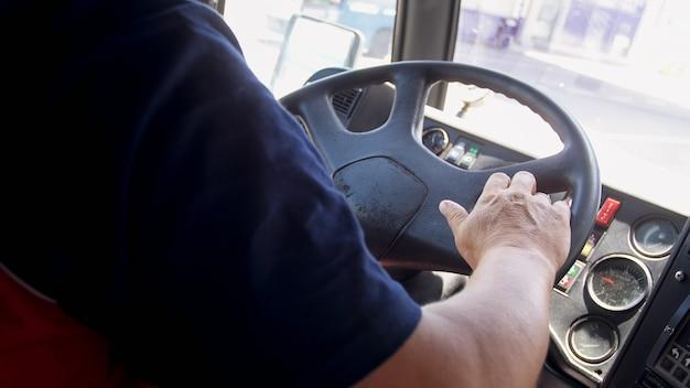 Крупным планом вид водителя автобуса мужского пола в аэропорту за рулем маршрутного автобуса.