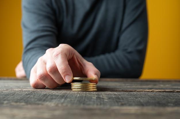 소박한 나무 책상에 황금 bitcoins 스태킹 남성 손의 근접 촬영보기.