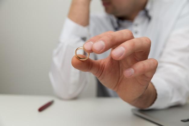 結婚指輪と男の手のクローズアップビュー。離婚の概念。