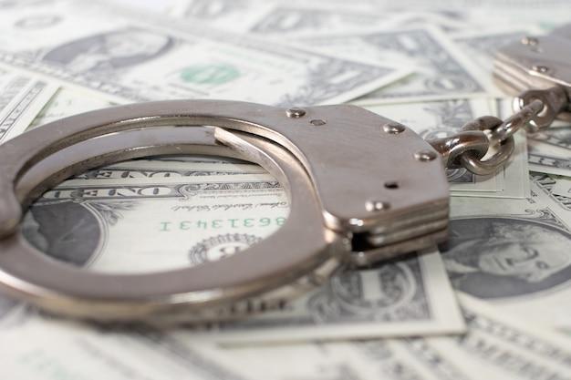 Крупным планом вид металлических наручников и долларов