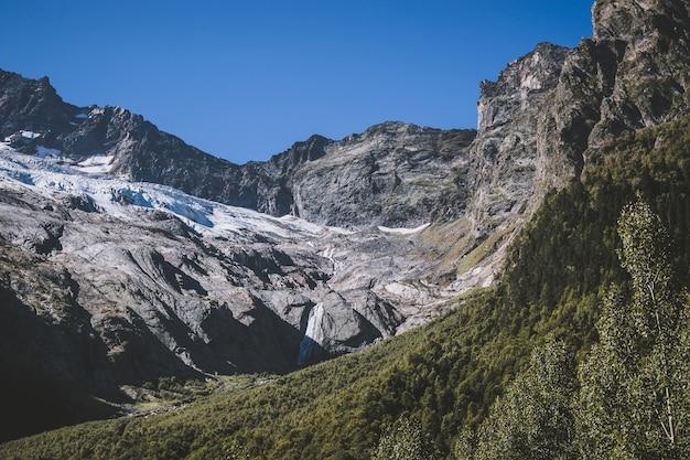 Крупным планом вид на горы в национальном парке домбай, кавказ, россия, европа. летний пейзаж и солнечное голубое небо