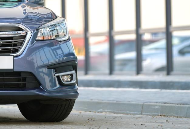 도시 거리 쪽에 주차된 반짝이는 값비싼 새 차의 클로즈업 보기.