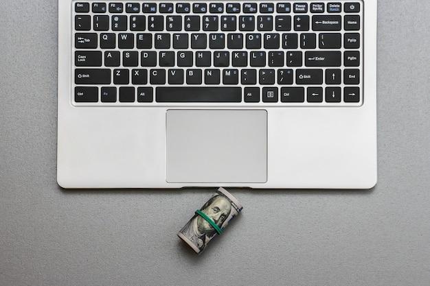 Крупным планом вид сто долларовых банкнот и клавиатуры ноутбука.