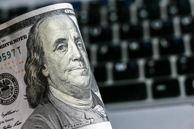 Крупным планом вид стодолларовых банкнот, клавиатура ноутбука в фоновом режиме.