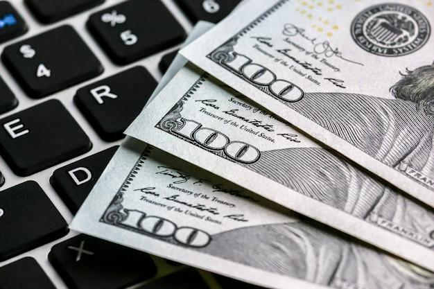 Крупным планом вид стодолларовых банкнот, лежащих на клавиатуре ноутбука.