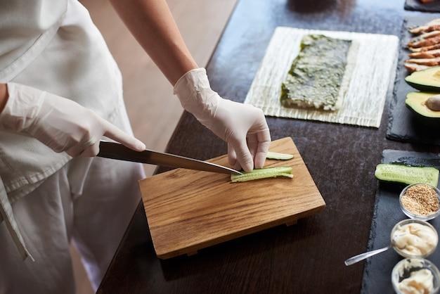レストランでおいしい巻き寿司を準備するプロセスのクローズアップビュー