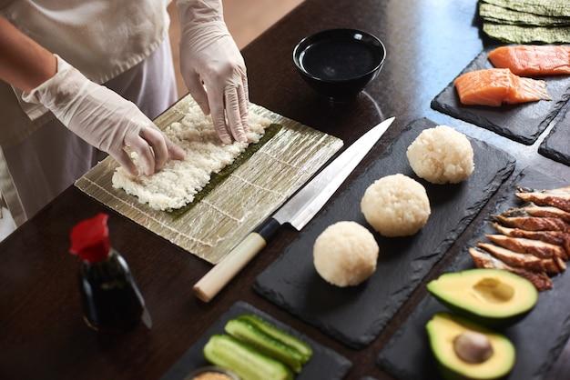 Крупным планом вид на процесс подготовки ролл суши. нори и белый рис. руки повара касаются риса. шеф-повар начинает готовить суши