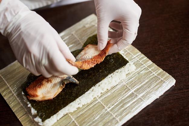 巻き寿司を準備するプロセスのクローズアップビュー。海苔、白ご飯、うなぎの竹マット。手袋をはめたシェフの手が巻き寿司の調理を開始