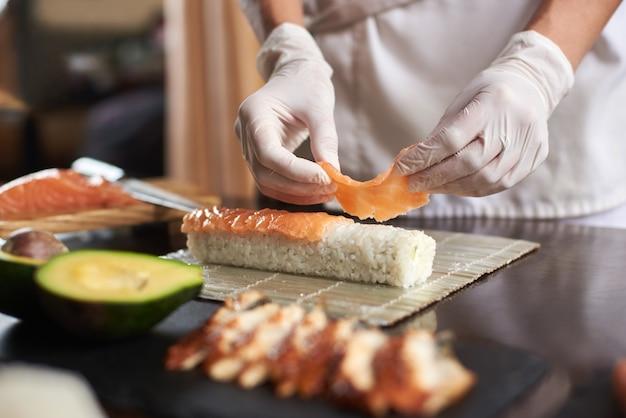 竹マットの上に使い捨て手袋で巻き寿司を準備するプロセスのクローズアップビュー