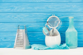 Closeup view of rag, bottle, pastry brush, grater, whisks and sieve in front of blue woode