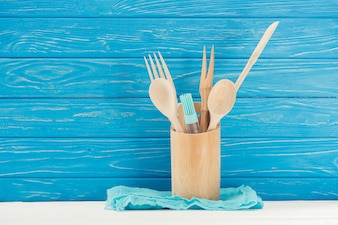 Closeup view of rag, pastry brush and kitchen utensils in front of blue wooden wall