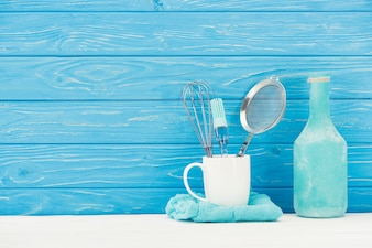 Closeup view of rag, whisk, sieve, pastry brush and bottle in front of wooden wall