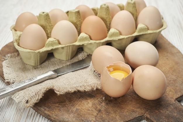 木製の背景に卵ボックスの生の鶏卵のクローズアップビュー有機卵ボックスの生の鶏卵...