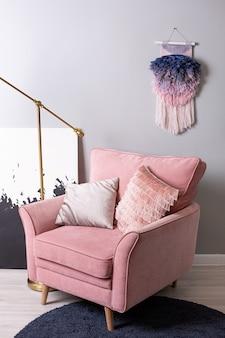 淡いピンクのスタイリッシュなアパートの側面図でバラの素敵なアームチェアとゴールドランプのクローズアップビュー