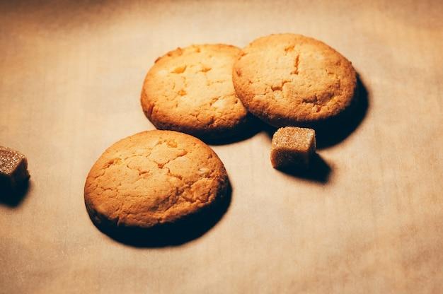 テクスチャードペーパーの背景にサトウキビの砂糖の立方体と丸いカリカリの甘いビスケットのクローズアップビュー