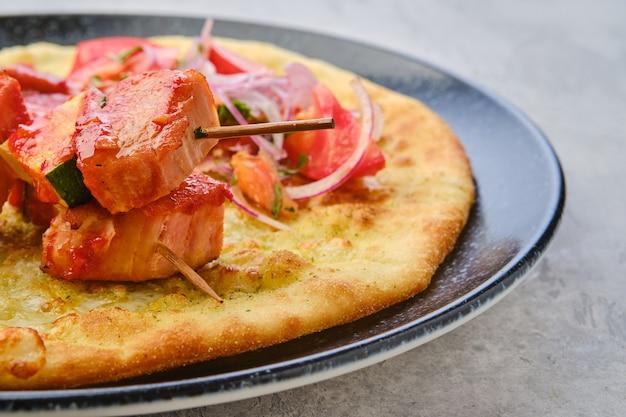 Крупным планом вид шашлыка, подаваемого на лепешке с помидорами и красным луком