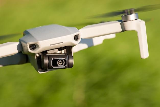 비디오를 촬영하고 측면으로 날아가는 작은 전문 드론의 근접 촬영보기
