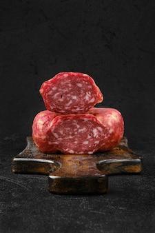 Крупным планом вид копченой колбасы на разделочной доске на черном фоне