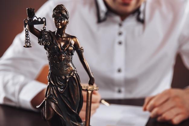 Крупным планом вид статуи правосудия. человек в белом шурте на заднем плане.