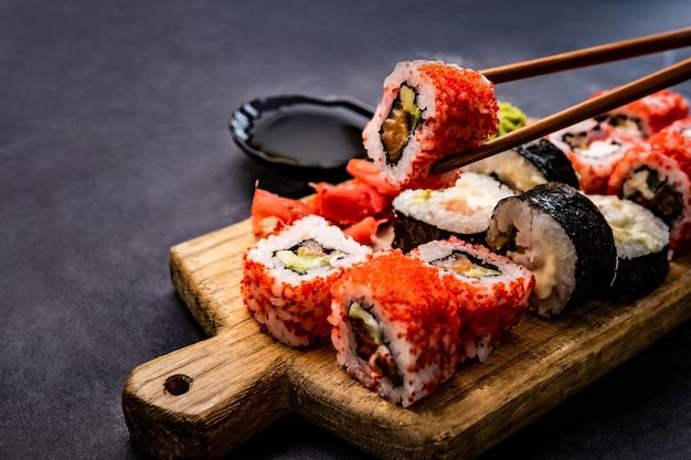 Крупным планом вид суши-маки, подаваемый на деревянном планшете, рука человека, держащего рулет с палочкой для еды, япония ...