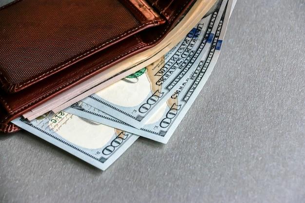 Крупным планом вид бумажник с банкнотами за сто пятьдесят долларов.