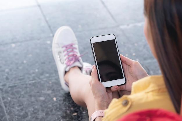 Крупным планом вид женщины, держащей черный экран смартфона, сидя на открытом воздухе