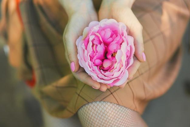 手に美しいピンクの花を保持している女性のクローズアップビュー。