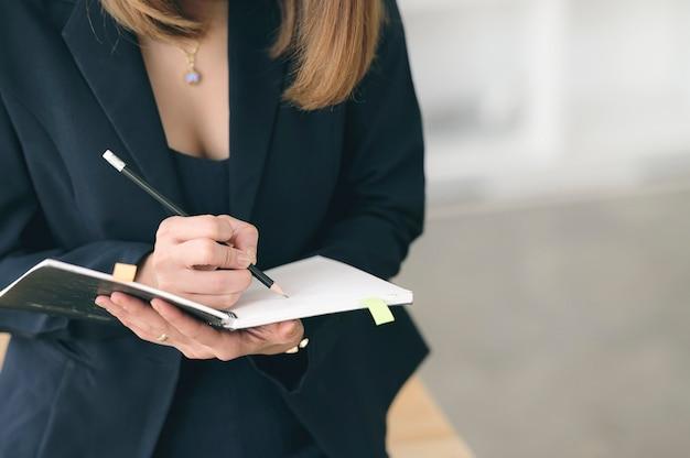 ノートに鉛筆書きを保持している女性のクローズアップビュー