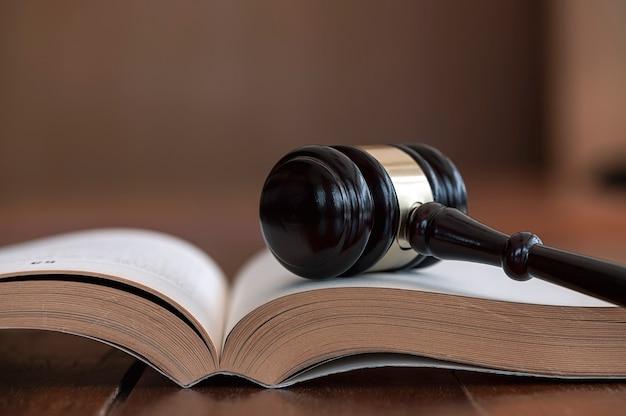 법률 책에 나무 판사 망치의 근접 촬영 보기.