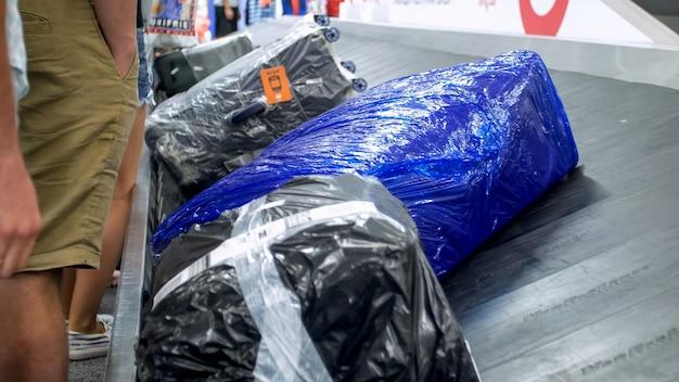 空港の手荷物受取所に横たわっているラップされたスーツケースのクローズアップビュー。