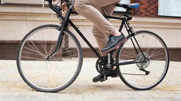 도시 거리에 빈티지 자전거를 타고 젊은 남자의 근접 촬영보기.