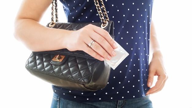 手にコンドームを保持している若い女性のクローズアップビュー。避妊とセックスの安全性の概念。