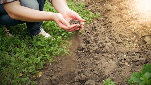 庭で乾いた大地や土を手に持っている若い女性のクローズアップビュー。