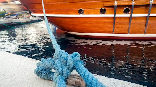 Closeup view of old wooden ship moored in sea port with blue rope.