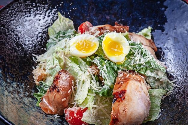 卵と肉のボウルと新鮮なサラダのクローズアップビュー。セレクティブフォーカスコピースペースのあるlucnhのフラットレイフード。メニューの写真。モダンシーザーサラダ