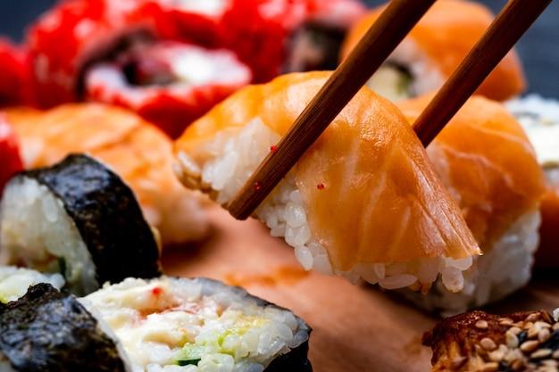 Крупным планом вид на съемочную площадку с суши-маки и сашими с сырой рыбой и лососем. человек подбирает традиционную японскую кухню.