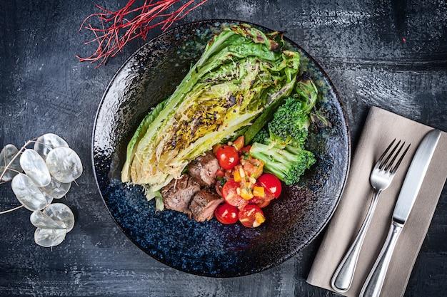 Взгляд крупного плана на теплом салате romain с томатом вишни и ростбифом служил в темной плите на темной предпосылке. плоская кладка еды. закройте вверх по взгляду на обеде с космосом экземпляра для дизайна.