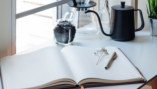 Closeup view of open notebook with blank page and pen on wooden table.